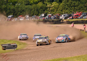 Cars racing around a dirt track followed by a plume of dust.